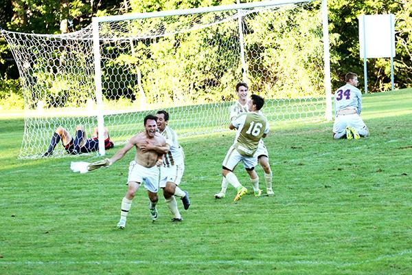 Sophomores Colin Michalski and Haven Mackie celebrate a game-winning goal with junior Colton Myers (16) and senior A.J. McNary against Shippensburg University the team went into double overtime for the victory.