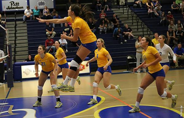 Pitt-Johnstown's red shirt junior outside-hitter Marissa Erminio in the air with a spike as teammates watch the play develop.