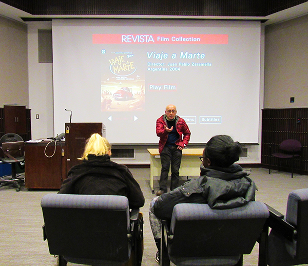 Professor Alvaro Bernal speaks to seniors Molly Dupin (left) and Erica Enarusai before the first film, Viaje a Marte, played in 131 Blackington Hall.