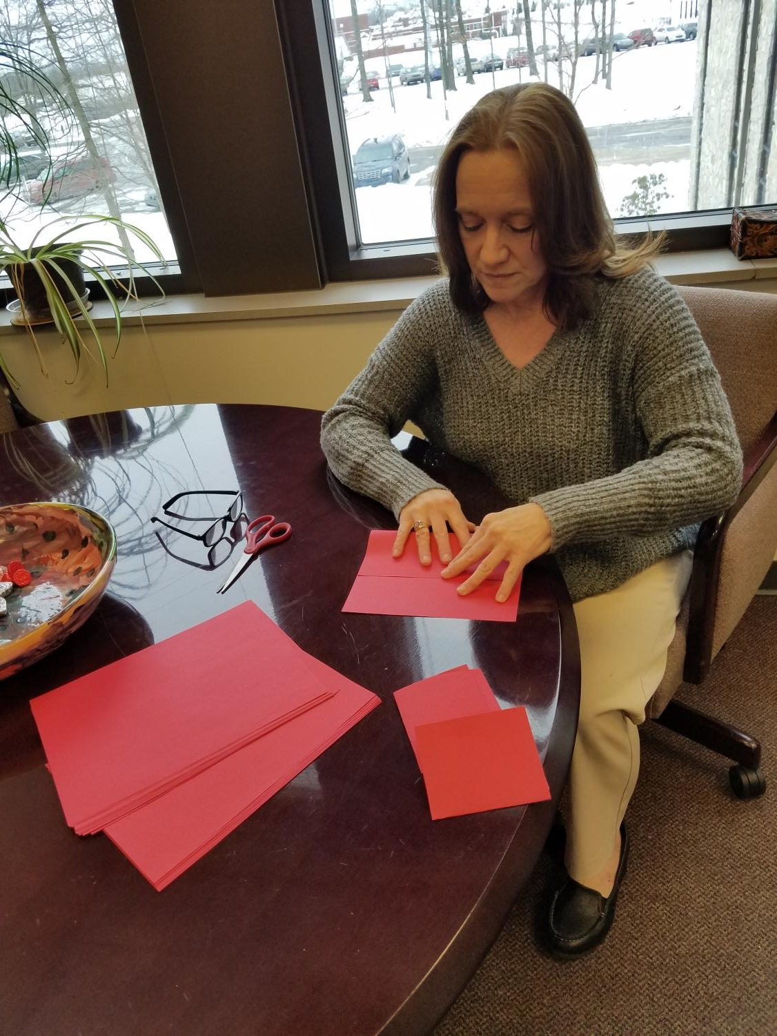 Assistant Academic Affairs Vice President Kristen Majocha makes red pockets with change in them Friday for Chinese New Year.