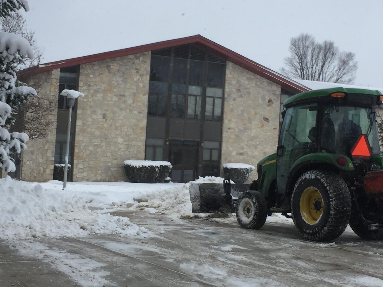 A grounds maintenance worker plows snow Jan. 30 off the sidewalk near Blackington Hall.