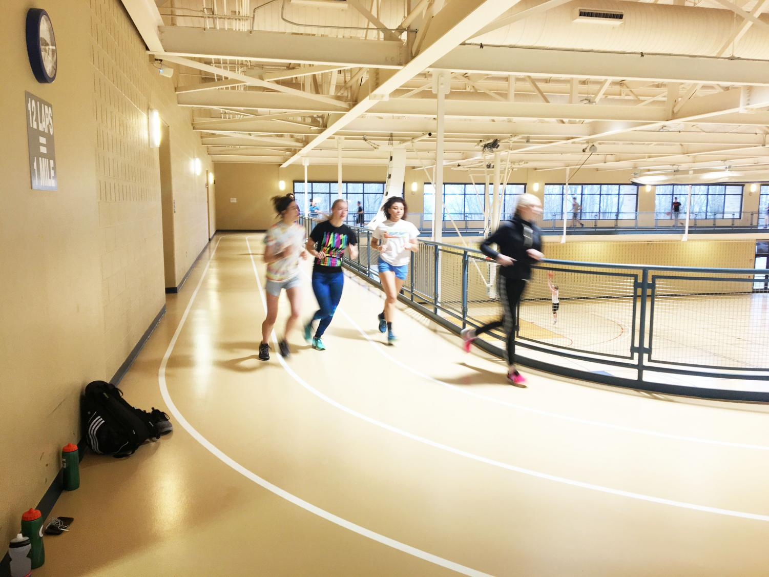 Track team members (left to right) Samantha Klutz, Alana Thomas, Taylor Briscoe and Samantha Miller run laps around the track in the Wellness Center last Friday.