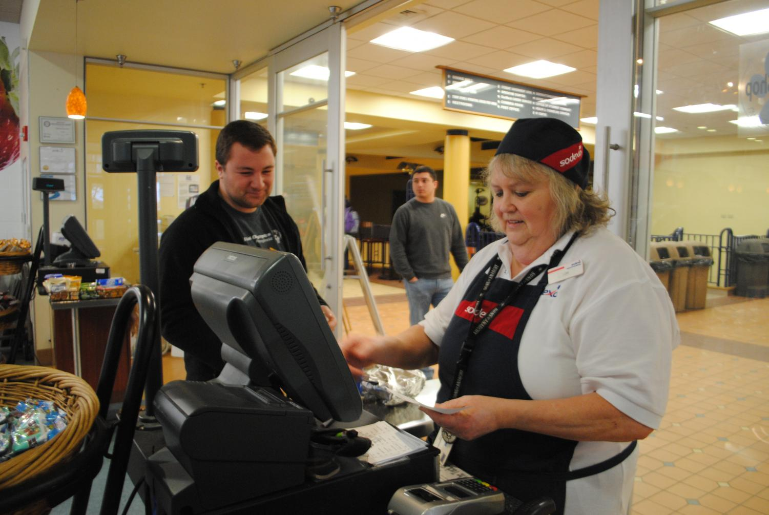 Senior Brady Willis pays Sodexo worker Lori Seigh for his food at the Tuck Shop.
