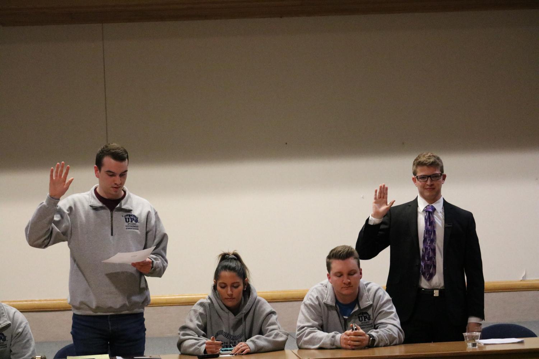 Former student government President Joe Evanko (left) swears in his successor Sam Miller (right) as president.