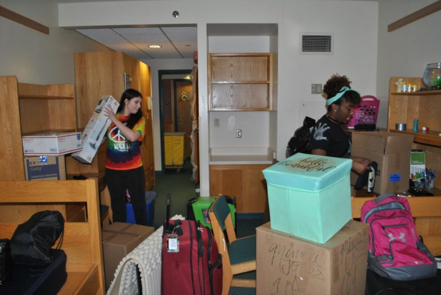 Sophomores+Brittney+Cesari+%28left%29+and+Minnie+Jones+%28right%29+pack+their+belongings+Oct.+7+out+of+their+first-floor+Living%2FLearning+Center+room.+