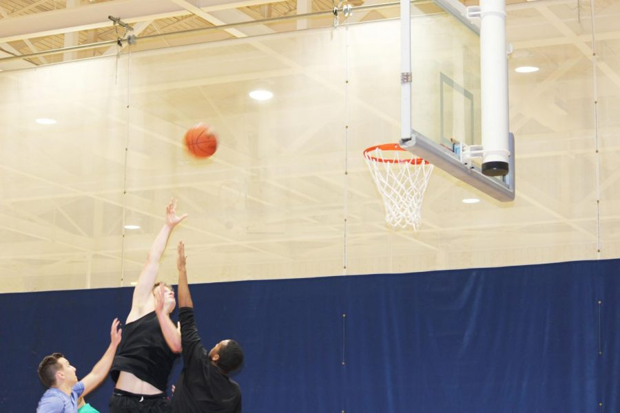 Matt+Holsinger+shoots+the+ball+against+two+oppenents+at+the+three+vs+three+basketball+helping+Melo+is+Trash+winning+the+game+Jan.+28+in+the+Wellness+Center.