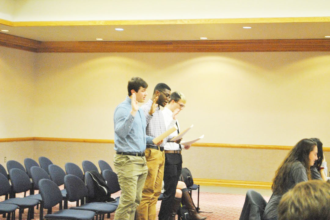 New student government senators Ryan Clark (left), Kyle Quartes Jr. (center) and Brant Durham (right) get sworn in during a Feb. 4 meeting.