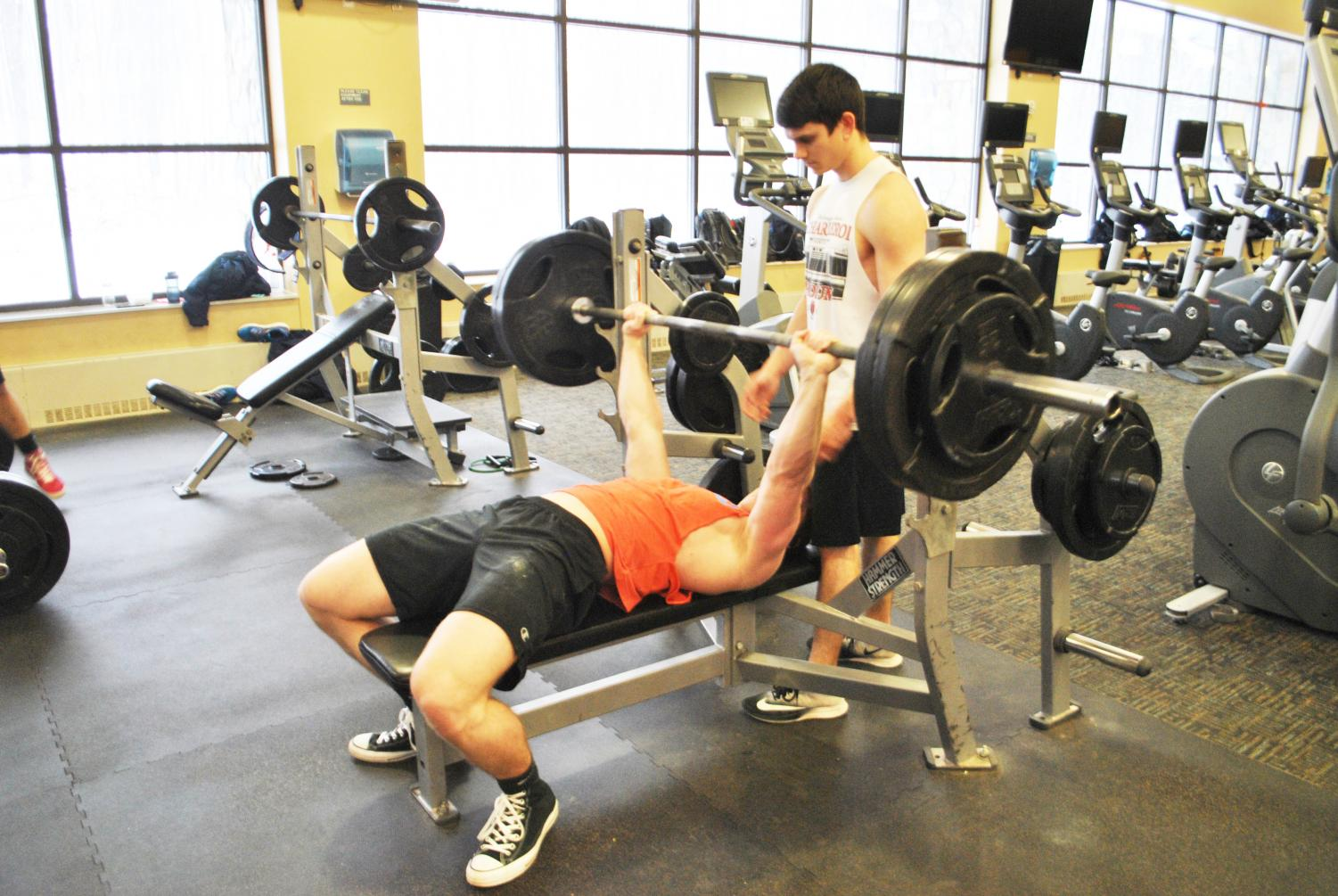 Senior Ethan Qualters lifts weight on the bench press as junior Nick Esola spots him in the Wellness Center on Friday.