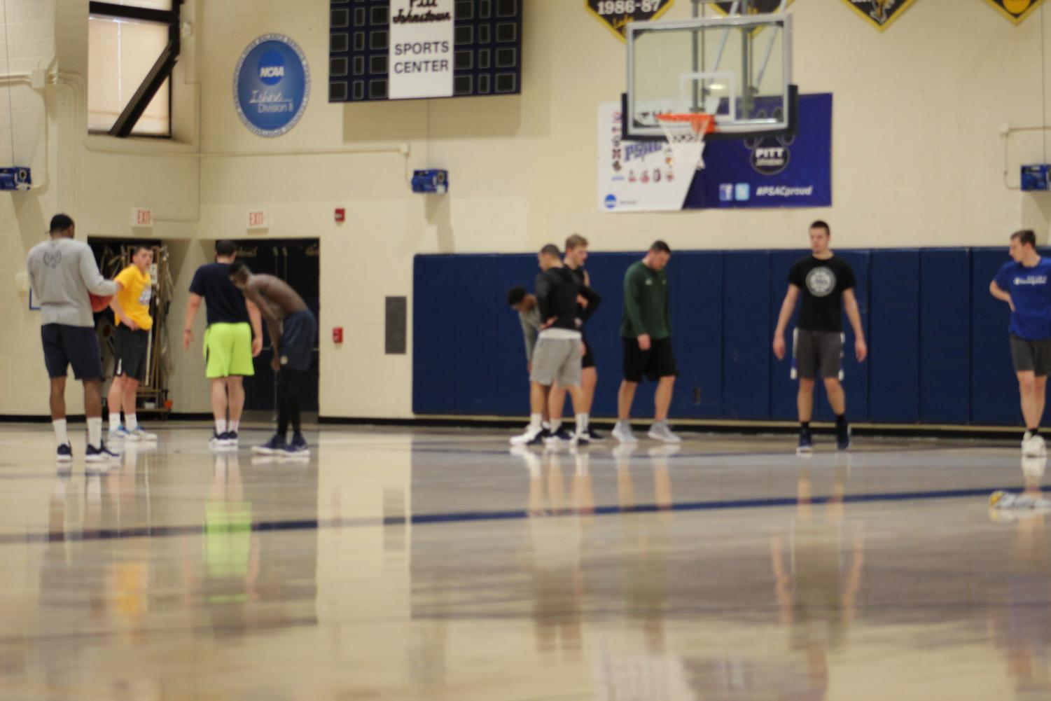 Women's head coach Mike Drahos second from right helps the men's basketball team for their pick-up game in the Sports Center March 20.