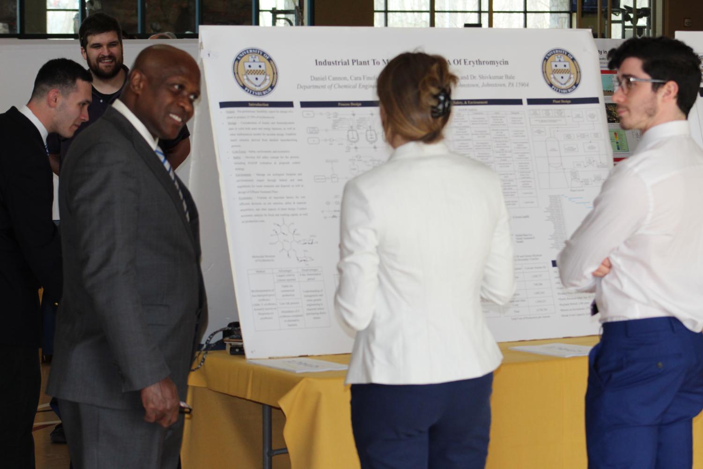 Pitt-Johnstown President Jem Spectar (left) views student research April 10 in the Wellness Center.