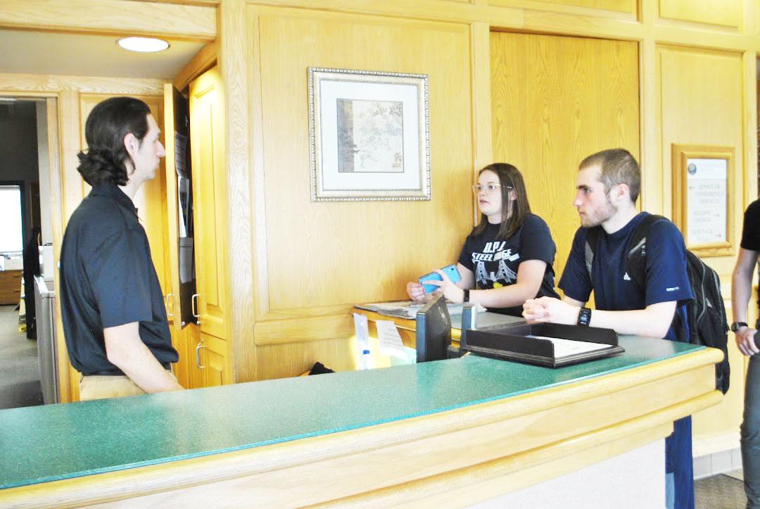 Sophomore Stephen Patterson (left) assists senior Rachel Stockert (center) and sophomore Garrett Pesi (right) last Friday in the Living/Learning Center.